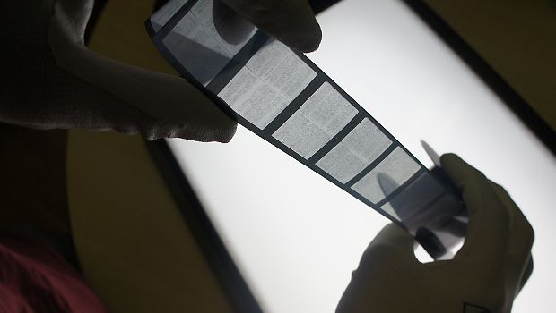 Imaging technician checking microfilm before digitising